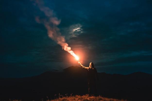 Человек, стоящий с палкой фейерверка на горе