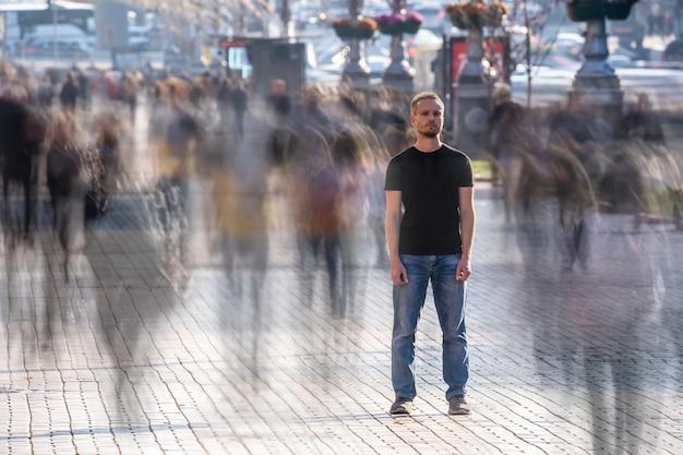 Мужчина стоит на людной улице