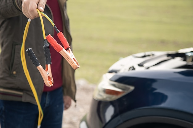 남자는 배터리를 점퍼하기 위해 차를 멈 춥니 다.