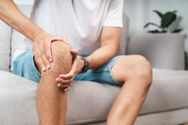 ソファに座って膝の痛みに苦しんでいる男性は、痛みを伴う膝をマッサージします。