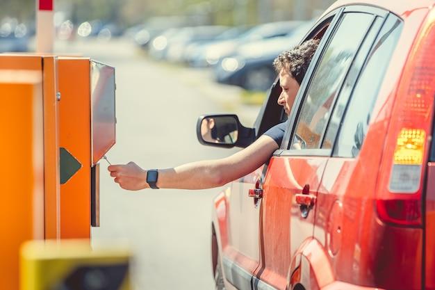 Мужчина берет парковочный талон при въезде на платную парковку на машине