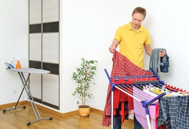 Мужчина снимает вещи с сушилки белья