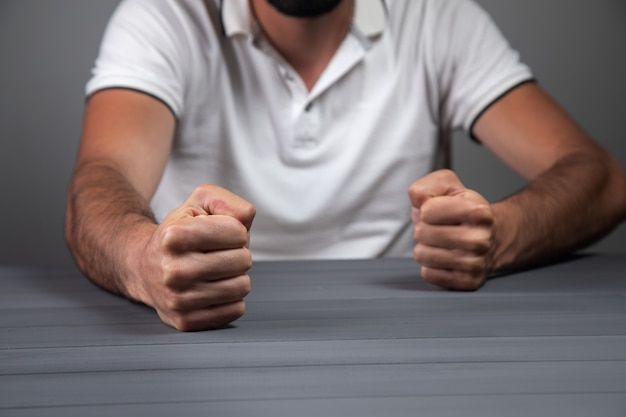 남자는 주먹을 테이블에 격렬하게 두 드린다.