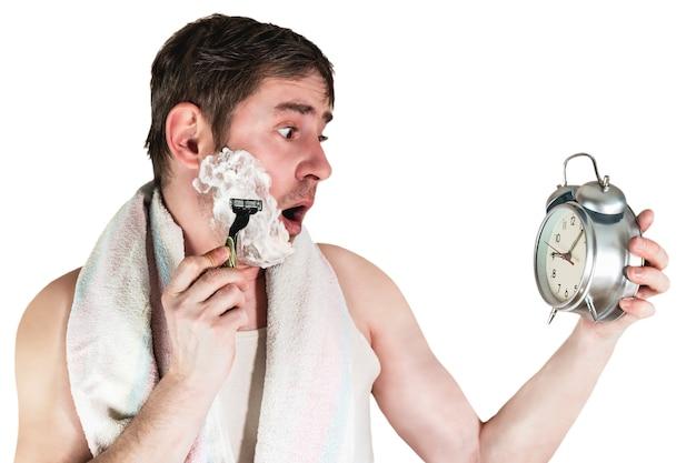 その男は朝仕事に遅れた。彼は古典的な目覚まし時計を手に持って、急いでリツォを剃ります。面白い表情。孤立した白い背景。