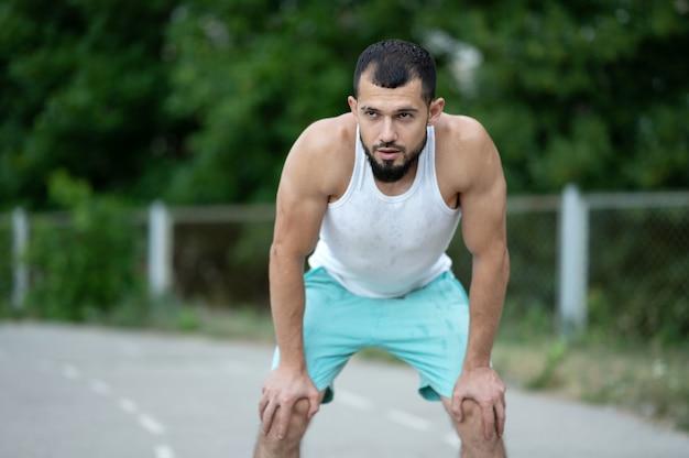Мужчина устал после тренировки. спортсмен восстанавливает дыхание