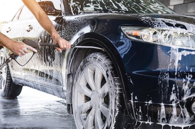 男は水圧で車から泡を洗い流す