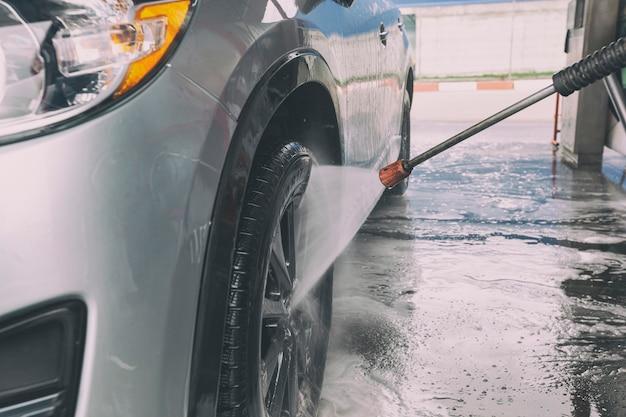 セルフサービスの洗車で車を洗う男