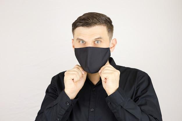 남자는 흰색 배경에 검은 의료 마스크를 착용