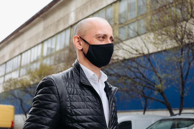 Мужчина в черной защитной маске. маска предотвращает заражение коронавирусом и пылью. новый тип коронавируса 2019-пневмония ncov человек в маске