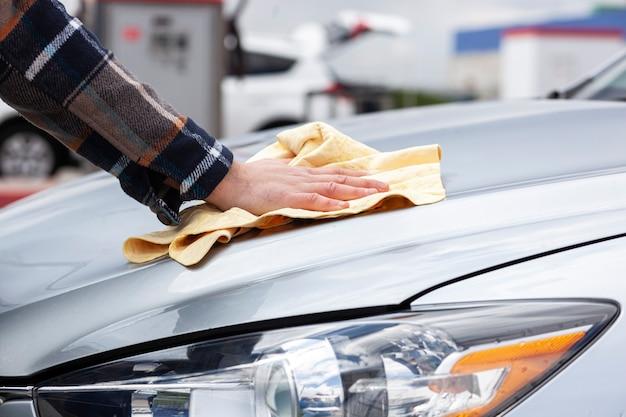 洗車で洗った後、車を拭く男
