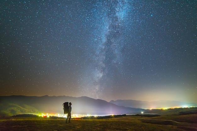天の川の背景にバックパックを背負った男が立っている。夜の時間
