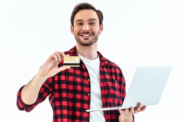 白い背景の上に立っているクレジットカードとラップトップを持つ男