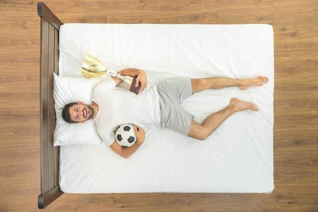 Мужчина с чашкой и мячом лежал в постели. вид сверху