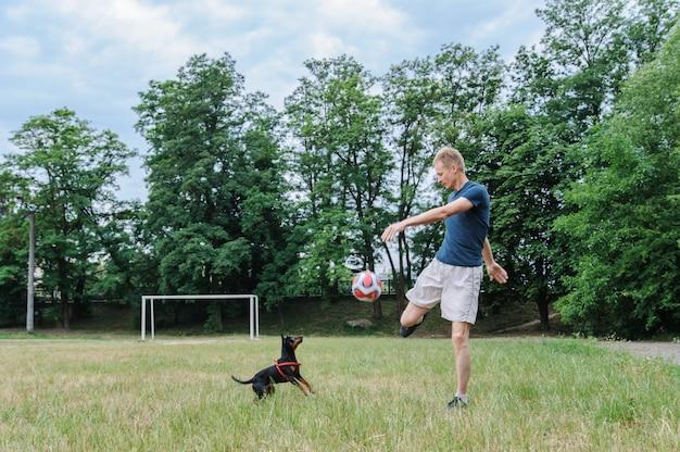Мужчина с собакой играет с футбольным мячом