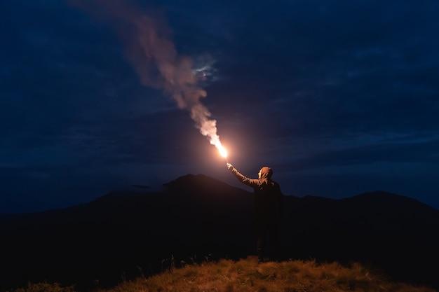 Человек с палкой фейерверка стоит на горе