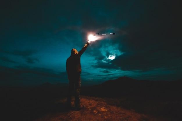 Человек с палкой фейерверка стоит на ночных горах
