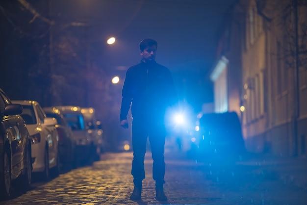 손전등을 든 남자가 거리에 서 있다. 저녁 밤 시간