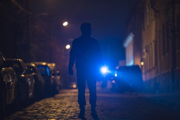 손전등을 가진 남자는 젖은 길에 서 있습니다. 저녁 밤 시간