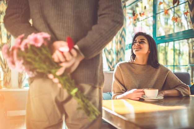Мужчина с цветами делает предложение своей женщине в ресторане