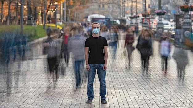 의료용 안면 마스크를 쓴 남자가 붐비는 도시 거리에 서 있다
