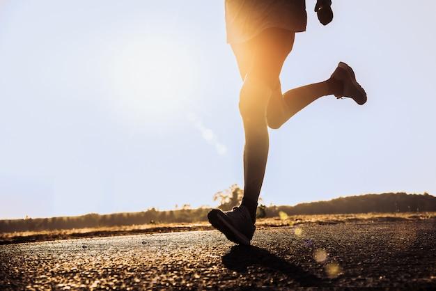 路上でランナーを持つ男は、運動のために走っています。