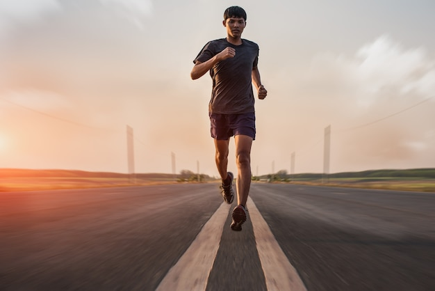 거리에 주자가있는 남자가 운동을 위해 달리고 있습니다.