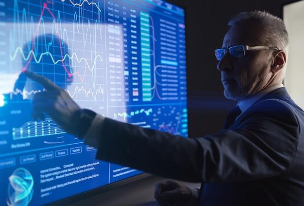 Человек, работающий на большом цифровом экране в темной комнате