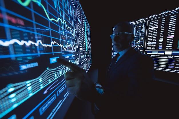 暗い実験室で大きなセンサーディスプレイに取り組んでいる男