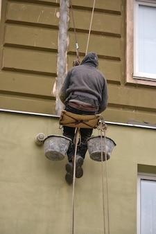 남자는 집의 클래딩 석고를 칠하는 고층 작업에서 일합니다.