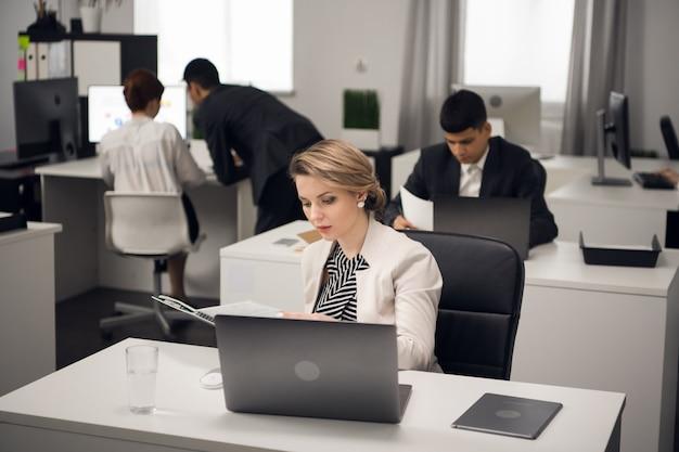 Менеджер занят офисной работой за письменным столом в открытом офисе большой компании.