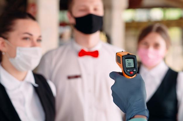 レストランやホテルのマネージャーは、熱画像装置でスタッフの体温をチェックします。