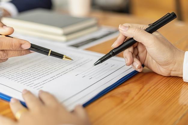 관리자는 근로계약서에 서명할 고용계약서를 가리키며, 지원자는 회사와 일하기 위한 계약서, 급여계약서 및 복리후생에 서명합니다.