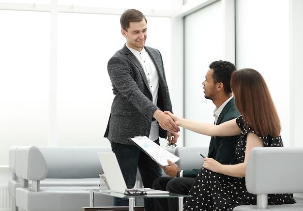 Менеджер встречает клиентов в холле банка.