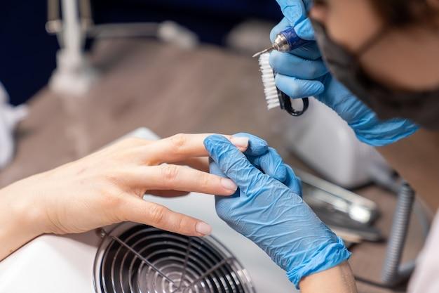 Мастер маникюра обрабатывает ногти клиента, придерживая аппарат и специальную щетку для очистки от пыли.