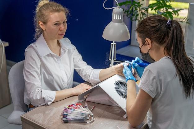 ネイリストは、新しいものを適用する前に、女の子の爪から古い光沢を取り除きます