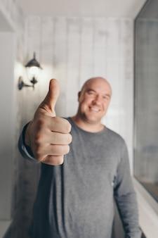 男の手は喜びの兆候を示しています手話は親指を立てる