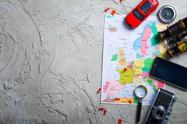 地図、飛行機、木製テーブルの上の旅行用品