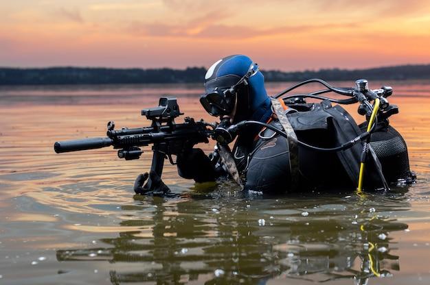海兵隊員は水から出てきて、武器を手にターゲットに向かって移動します。ビデオゲーム、広告、世界の不安定さ、国の対立の概念。ミクストメディア
