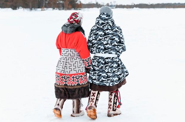 Семейная пара идет по снегу. праздник дня северного оленя народов севера.