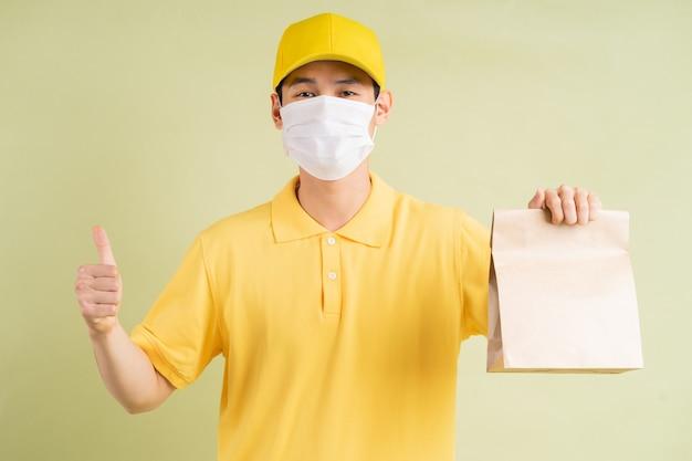 仮面をかぶったアジア人の配達人が紙袋を持って親指を持っていた