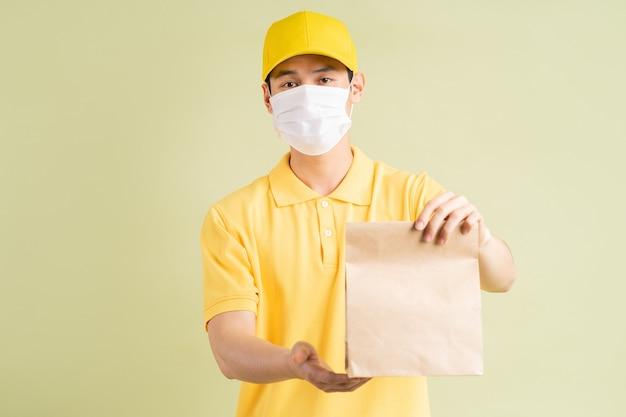 仮面のアジア人配達人が紙袋を持っていた