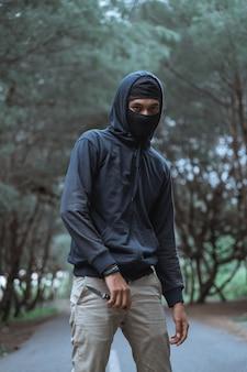 Человек в маске с ножом в черном стоит посреди дороги в лесу