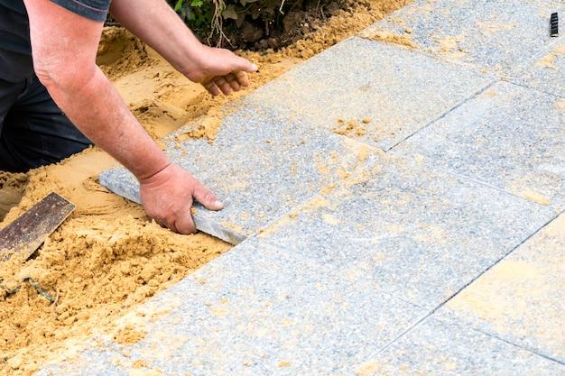 メイソンは砂利のスラブを砂の上に置き、路地を作ります