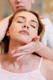 マッサージ療法士は首のマッサージをします