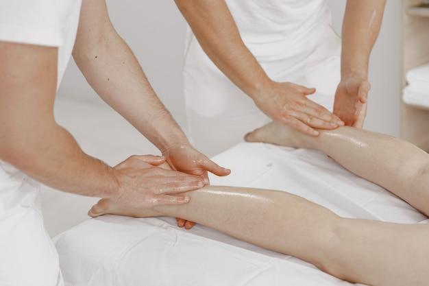 Массаж в четыре руки. концепция здравоохранения и женской красоты. две массажистки делают двойной массаж девушке. женщина в спа-салоне.