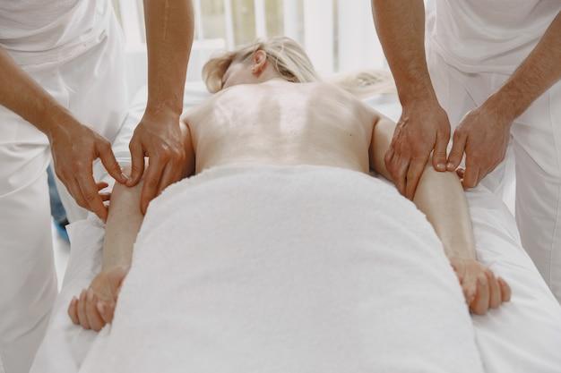 네 손으로 마사지합니다. 건강 관리 및 여성의 아름다움의 개념. 두 명의 안마사가 여자를 두 번 마사지합니다. 스파 살롱에서 여자입니다.