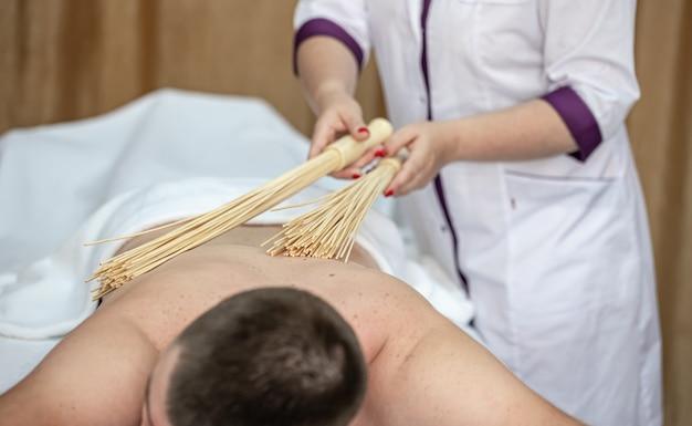 Массажист делает мужчине японский массаж бамбуковыми вениками.