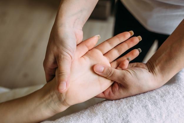 マッサージ師がスパで女性の手にマッサージをします