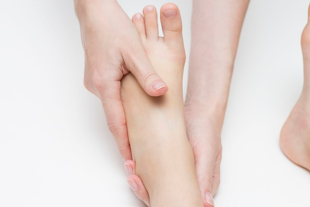 Массажист выполняет девушке массаж стоп. ортопедия. вальгусное и плоскостопие.