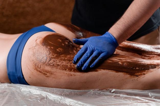 안마사는 스파 센터에있는 소녀의 다리와 허벅지에 초콜릿을 바릅니다. 미용 절차 초콜릿 랩.
